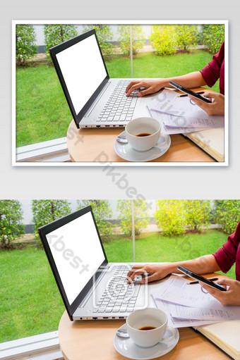 Empresaria escribiendo en una computadora portátil con pantalla en blanco en blanco para simular el fondo de la plantilla y Fotografía Modelo JPG