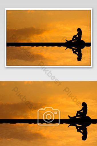 silueta de mujer asiática sentada y buscando algo en la montaña Fotografía Modelo JPG