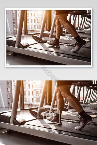 Cerca del deporte hombre corriendo en cinta en el gimnasio en condominio en la población urbana Fotografía Modelo JPG