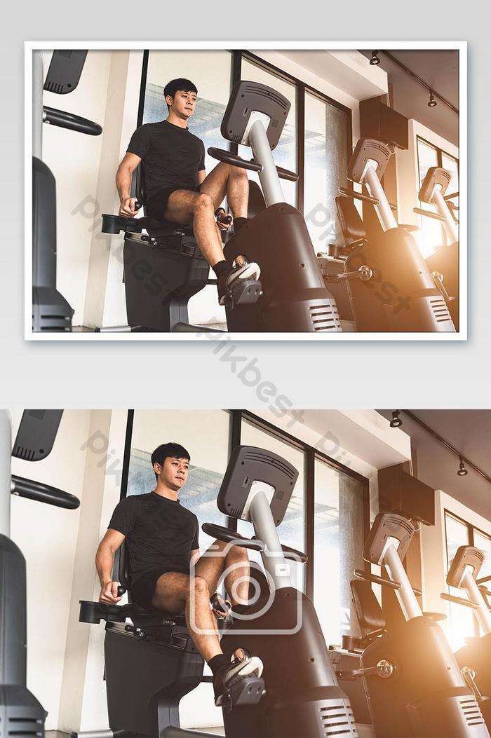 피트니스 체육관에서 고정식 자전거를 타는 아시아 젊은 스포츠 남자 회전 운동을하는 남자