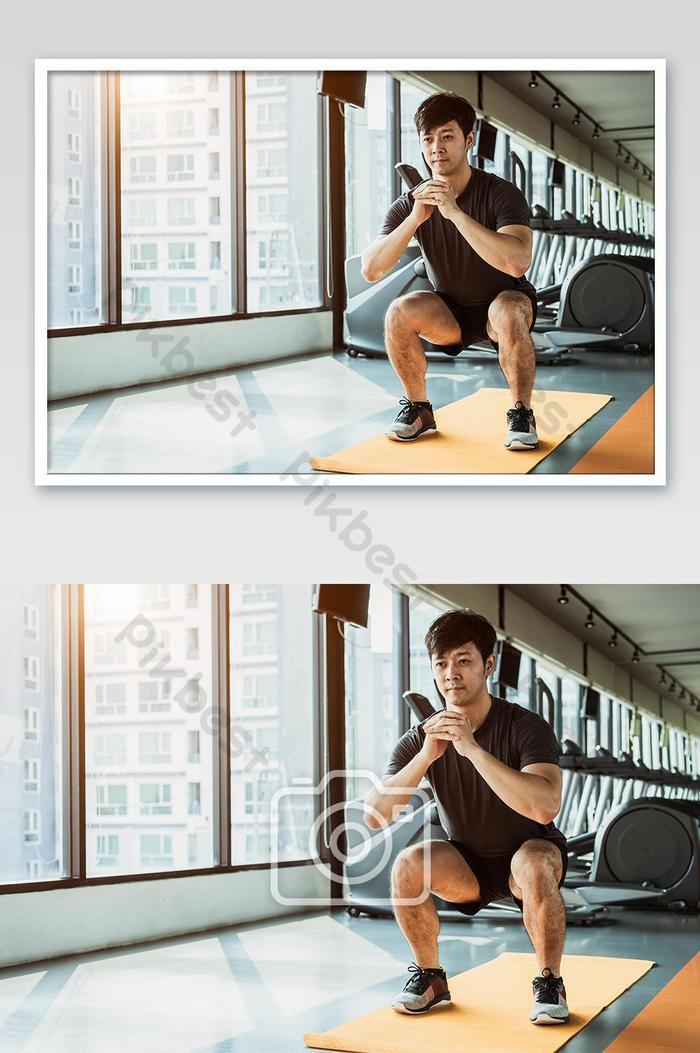 도시의 콘도에서 피트니스 체육관에서 요가 매트에 쪼그리고 앉는 자세를하는 스포츠 남자