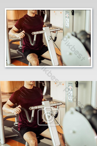 Front view of sport man using back muscle stretch machine called seated row in fitness gym Photo Template JPG