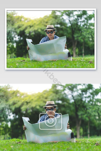 A happy traveler senior man sit in Forrest, opening a map Photo Template JPG