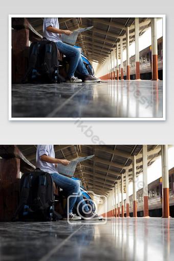 Voyageur portant un sac à dos tenant une carte en attente d'un train et de la planification du prochain voyage La photographie Modèle PSD