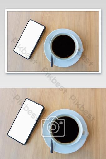 teléfono inteligente con pantalla blanca en blanco para simular el fondo de la plantilla y una taza de café Fotografía Modelo JPG