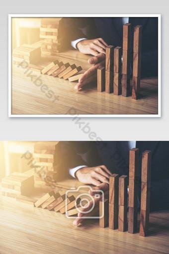 Pengusaha tangan menghentikan efek domino kayu yang jatuh dari risiko atau terguling terus menerus Fotografi Templat JPG