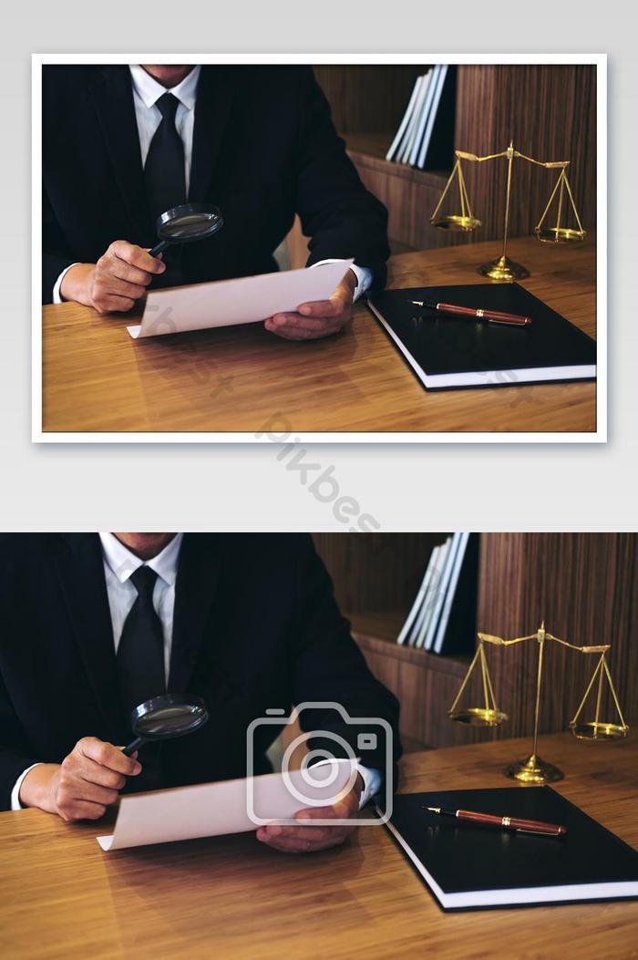 peguam lelaki membaca perjanjian kontrak sah dan memeriksa dokumen dengan kaca pembesar