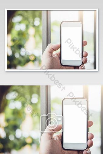 Imagen de maqueta de la mano del hombre sosteniendo un teléfono inteligente blanco con pantalla en blanco sobre fondos de naturaleza Fotografía Modelo JPG