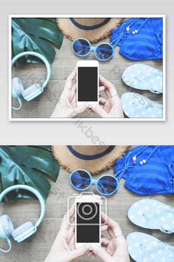 Vista superior de las manos de la mujer con smartphone con artículos de verano en el fondo Fotografía Modelo JPG
