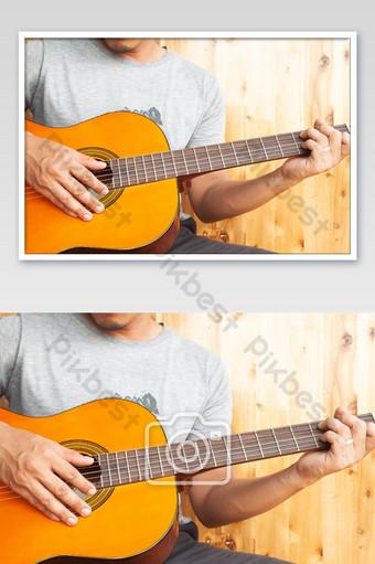 قرب رجل آسيوي يلعب الغيتار الصورة التصوير قالب JPG