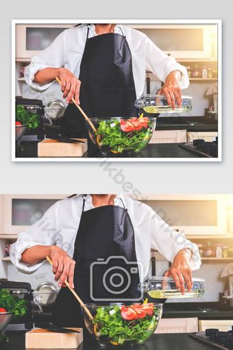 امرأة شابة السعادة تطبخ سلطة الخضار في صورة المطبخ التصوير قالب JPG