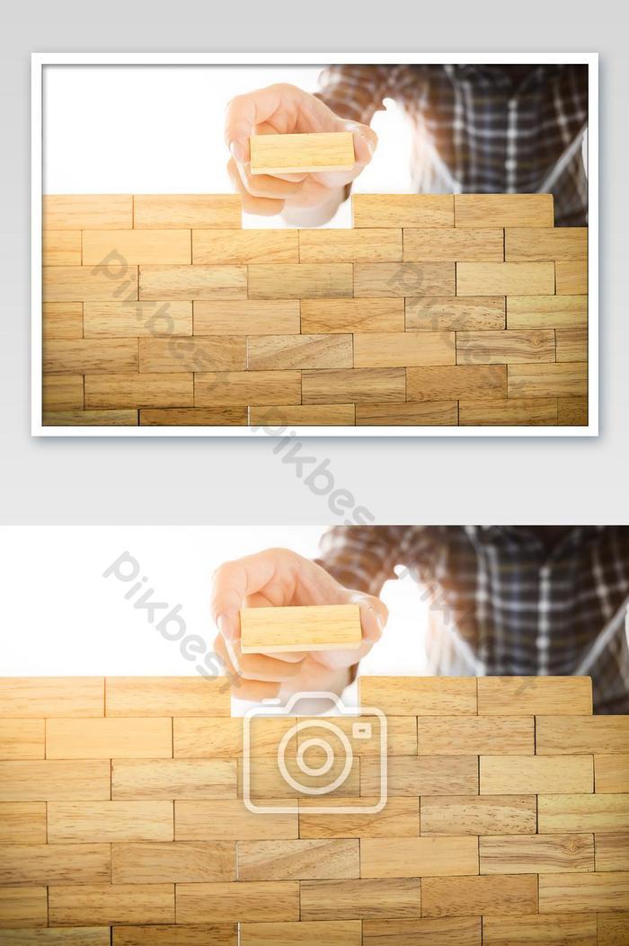 มือของวิศวกรเล่นเกมบล็อกไม้ทาวเวอร์ jenga บนพิมพ์เขียวหรือสถาปัตยกรรม