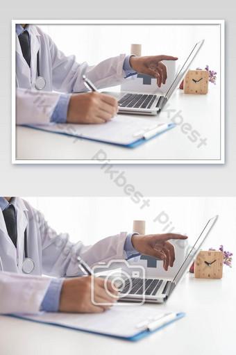 醫生使用便攜式計算機並在文書工作醫院背景照片上寫 攝影圖 模板 JPG