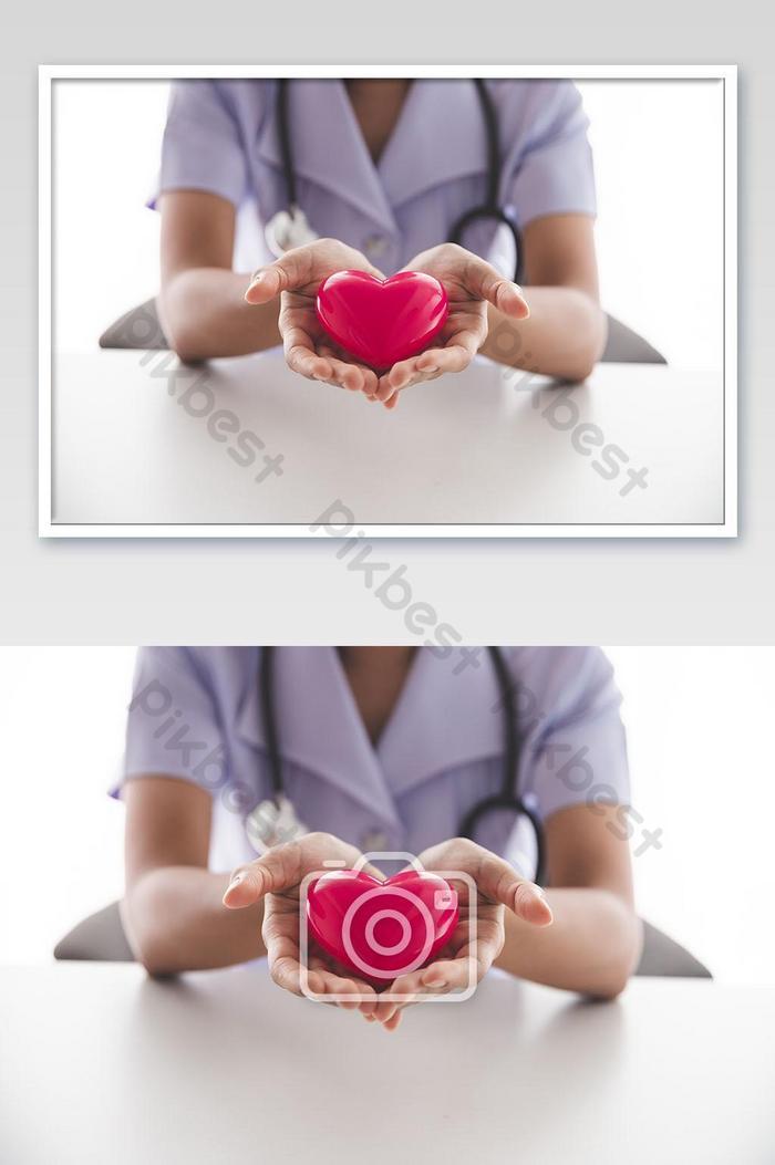 femme médecin avec stéthoscope tenant coeur sur fond clair