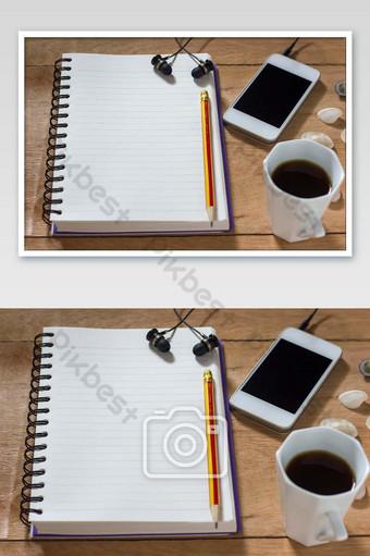 دفتر بنك مع قلم رصاص على طاولة بنية اللون أبيض مع صورة سماعات التصوير قالب JPG