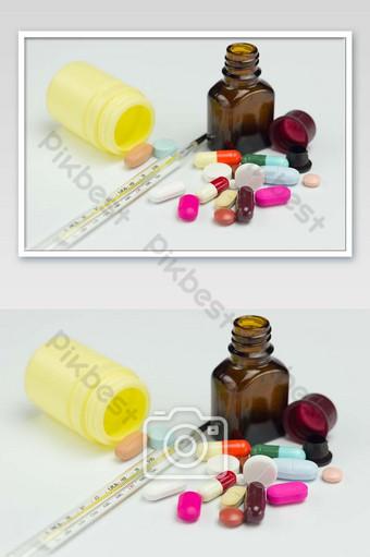 حبوب الدواء المضادات الحيوية الملونة أو كبسولات ومقياس الحرارة على صورة خلفية بيضاء التصوير قالب JPG
