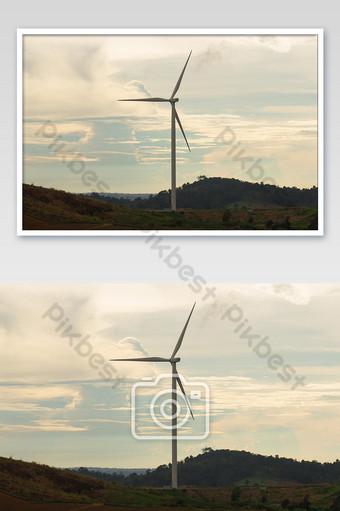 silueta de turbina eólica en la montaña al atardecer foto de energía renovable Fotografía Modelo JPG
