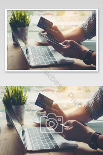 Hombre que sostiene el pago con tarjeta de crédito de compras en línea en un teléfono inteligente Fotografía Modelo JPG