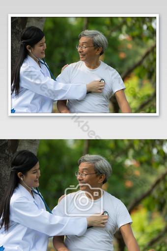 الطبيب الذي يستخدم سماعة الطبيب يستمع إلى نبض قلب المريض المسن صورة حديقة المستشفى التصوير قالب JPG