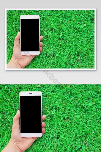 Image de maquette de mains tenant un téléphone mobile blanc en toile de fond d'herbe verte La photographie Modèle JPG