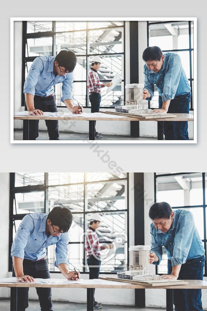 มือของสถาปนิกหรือวิศวกรที่ทำงานในการประชุมพิมพ์เขียวสำหรับรูปถ่ายทำโครงการ