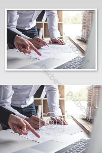 Les mains des ingénieurs travaillant sur le plan de construction et le modèle de construction sur un lieu de travail La photographie Modèle JPG