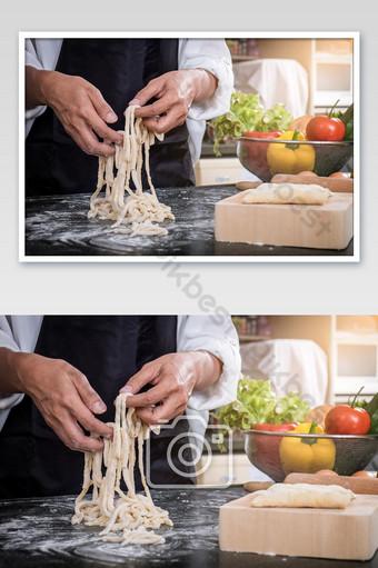ربة منزل تصنع المعكرونة محلية الصنع بالدقيق والبيض فوق الطاولة في صورة المطبخ التصوير قالب JPG