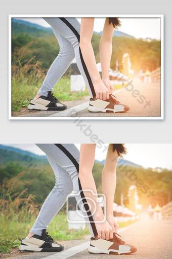 Disparo de joven corredor apretando los cordones de las zapatillas para correr preparándose para trotar Fotografía Modelo JPG