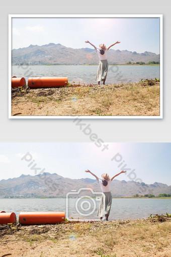 Người phụ nữ châu Á hạnh phúc trong trang phục giản dị giơ cánh tay đứng trên sông Nhiếp Ảnh Bản mẫu JPG