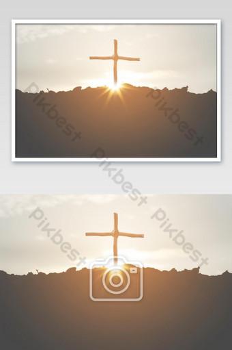 Crucifixión cruzada de Jesucristo en una silueta de montaña con un fondo de puesta de sol Fotografía Modelo JPG