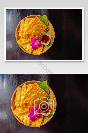 siomay goreng kuning dan secangkir saus di atas piring bambu di hiasi dengan anggrek Fotografi Templat JPG