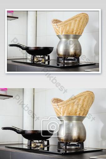 قم بتشغيل موقد الغاز لطهي الأرز اللزج بالبخار وطهيه في المطبخ التصوير قالب JPG