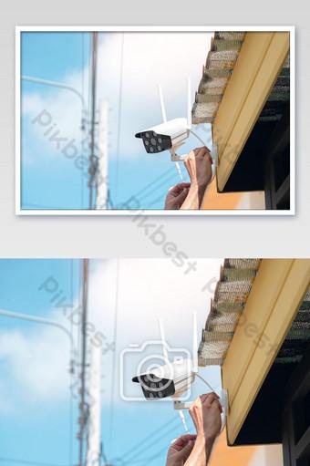 يقوم الفنيون بتركيب كاميرا مراقبة لاسلكية في مقدمة المنزل التصوير قالب JPG