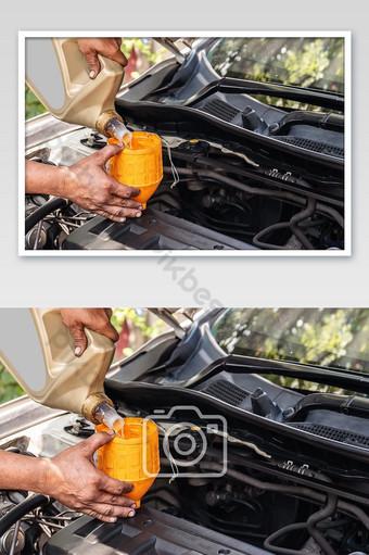 ميكانيكي السيارة يضيف النفط إلى صناعة السيارات ومفاهيم المرآب التصوير قالب JPG