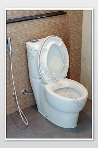 Gros plan de la toilette de chasse en céramique dans la belle salle de bain design La photographie Modèle JPG