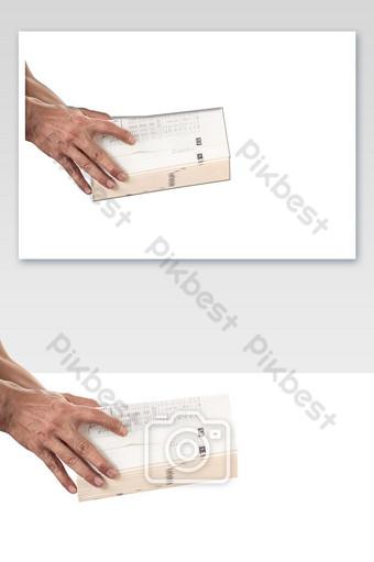 Gros plan de la main de l'homme tenant et ouvrant un livre épais sur fond blanc Éléments graphiques Modèle PNG