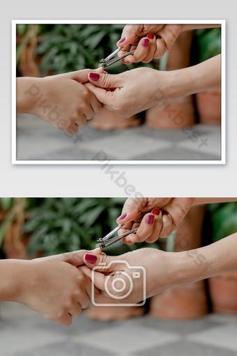 Gros plan une main femme utilise une tondeuse à ongles pour couper les ongles d'enfants La photographie Modèle JPG