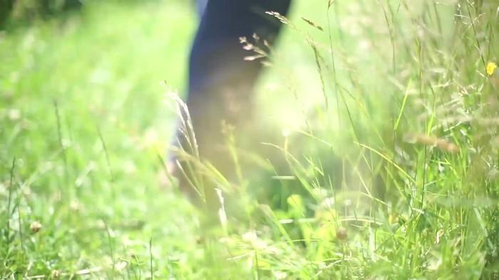 video quay thực 4k của người phụ nữ đi trên cỏ